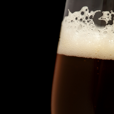freshly poured dark beer in a taster glass, isolated on black