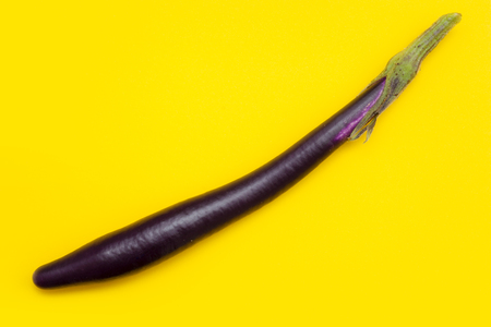 food abstract with aubergine, long variety, on bright yellow surface