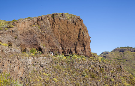 Gran Canaria, June, steep walls of  ravine Barranco de Guayadeque, caves in volcanic rock Banco de Imagens