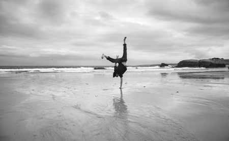 young man on a wet sandy beach doing acrobatics, monochrome image