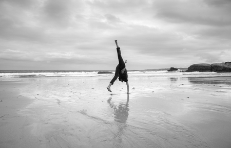 young man doing acrobatics on a beach