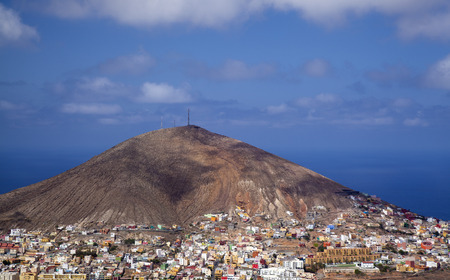 Gran Canaria, view towards volcanic cone of Montana de Galdar, its base surrounded by small multicolored houses of Galdar town 版權商用圖片