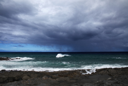 Gran Canaria, Puertillo de Banaderos area, dark lava coast and rain over ocean