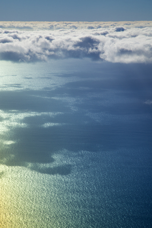 natural sky, clouds and sea surface background from low flying plane, rainbow effect on the water Banque d'images