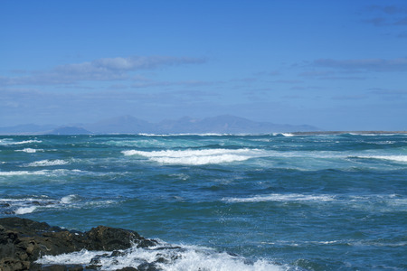 Fuerteventura, view from Faro de Toston across Majanicho bay towards Lanzarote on the horizon, stormy ocean