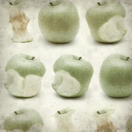 textured old paper background with green apple eating progression