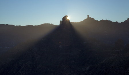 Gran Canaria, December, Las Cumbres,  amazing winter solstice sunrise over rock formation Roque Bentayga as seen from Acusa Seca, the rock throwing a cone of shadow, first ray of sunlight