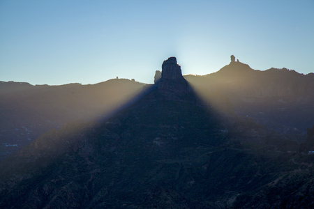 Gran Canaria, December, Las Cumbres,  amazing winter solstice sunrise over rock formation Roque Bentayga as seen from Acusa Seca, the rock throwing a cone of shadow
