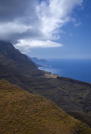 Gran Canaria, March, landscapes of Agaete municipality, hiking route San Pedro - Puerto de las Nieves, view towards Faneque, Europe tallest cliff above sea level, and curvy and dangerous road Agaete - La Aldea de San Nicolas Foto de archivo