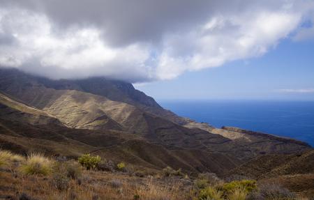 Gran Canaria, March, landscapes of Agaete municipality, hiking route San Pedro - Puerto de las Nieves, view towards Faneque, Europe tallest cliff above sea level, and curvy and dangerous road Agaete - La Aldea de San Nicolas