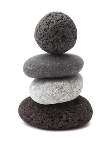 small zen pyramid of dark Canarian lava pebbles isolated on white