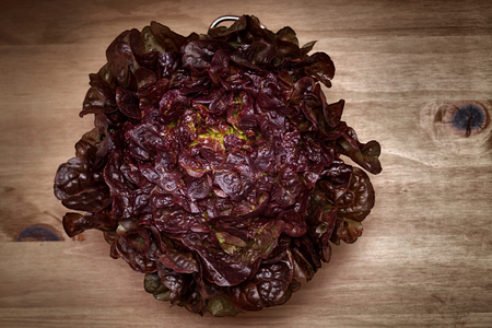red leaf lettuce in a colander on wood board background Imagens