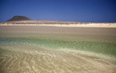 La Graciosa island, part of Chinijo Archipelago,  view across shallow lagoon Bahia del Salado towards Montana Amarilla, Yellow Mountain