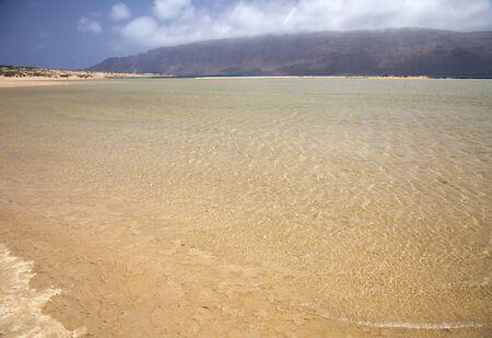 La Graciosa island, part of Chinijo Archipelago,  view across shallow lagoon Bahia del Salado and further El Rio strait towards Famara massif on Lanzarote Фото со стока