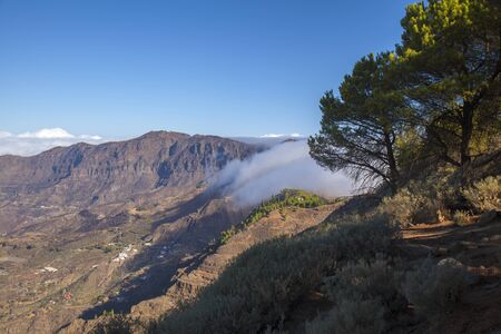 Gran Canaria, October, clouds flowing into Caldera de Tejeda from the right over mountain pass Cruz de Tejeda, Los Moriscos cliffs affected by wildfire of summer in the background