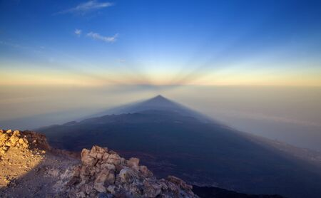 Sunrise on Teide, the tallest mountain of Spain and Atlantic Basin, view west towards  shadow of volcano cast onto the morning mist, lower levels of Tenerife visible, anticrepuscular rays in the sky