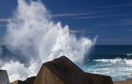 Gran Canaria, waves breaking against seawall in Puerto de Las Nieves, flying foam