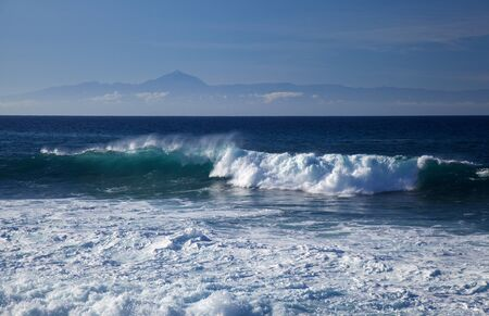 Gran Canaria, powerful waves breaking in Puerto de Las Nieves, flying foam, Teide on Tenerife in the background