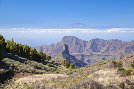 Gran Canaria, January, view along a small valley, rock formation Roque Bentayga,mountain range Altavista and Teide on Tenerife lined up