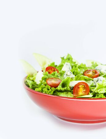 Vegetarian salad with tomatoes, cheese, lettuce. Vegetables in the red bowl. Delishes food. Stock Photo