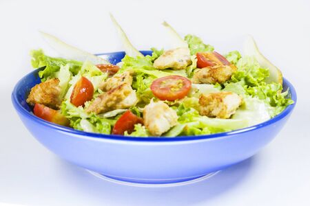 Chicken salad with tomatoes, pear and green salad on the blue bowl, white background. Imagens