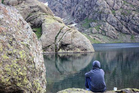 Hiker sitting on the stone near mountain lake