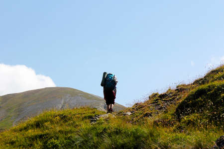 Hiker on the mountain landscape background, young girl backpacker in mountain. Georgian nature. Beautiful woman travel scene.