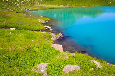 Alpine mountain lake landscape and view, blue beautiful and amazing lake panorama, wide angle lens landscape and mountain reflections in Okhrotskhali in Svaneti, Georgia.