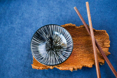 Empty Asian dishware, bowl, pate and chopsticks on the blue background, restaurant tableware