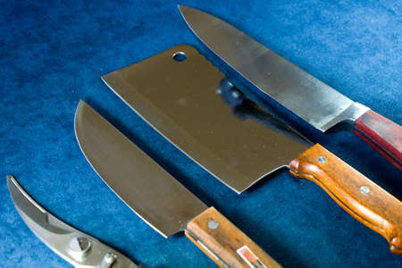Kitchen knives collections on the blue background, tools and instruments for cooking.