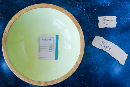 One bowl on the blue background and old paper with receipt.