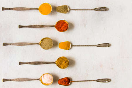 variation of spices on the vintage silver spoons, all spices on the table, colorful food background