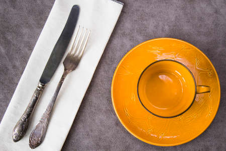 Empty orange tableware and dishware settings and serving on the gray background, plate, cup, folk and knife
