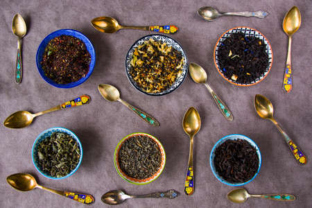 Herbal and natural dry tea set, variation and collection of tea and vintage spoons, high angle view
