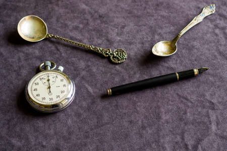 Vintage pocket clock, fountain pen and spoons on the table 免版税图像