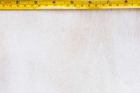 Tape measure centimeters and millimeters on the yellow ruler. Sizes on the white background Foto de archivo