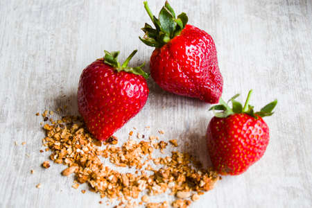 Red raw strawberry on the table and granola, morning breakfast food close-up 免版税图像