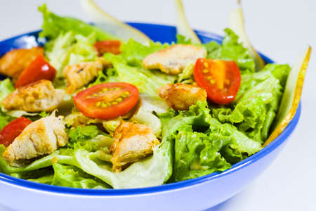 Chicken salad with greens, tomatoes and apple in the blue bowl