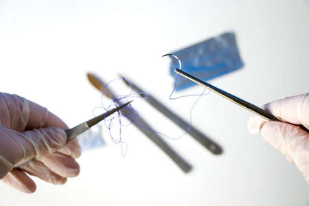 Surgery operation equipment, scalpel, knife, suture and needle on the white background. Studio shoot.