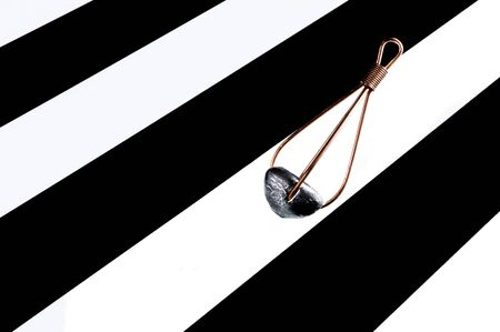 feeder: Lead fishing feeder on black and white stripe background