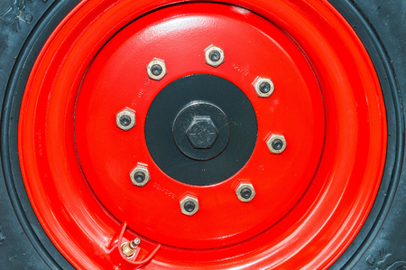agriculture machinery: Large red wheel rim, for machinery used in agriculture. Detail.