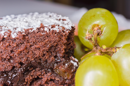 Chocolate sponge cake with icing sugar and grapes. Stock Photo