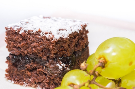 Chocolate sponge cake with icing sugar and grapes on the beige tablecloth. Stock Photo