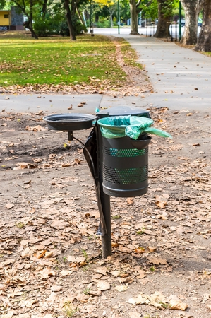 Metal trash can in the park in autumn.