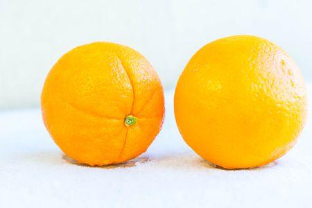 Two orange on snow background. Ripe fruits