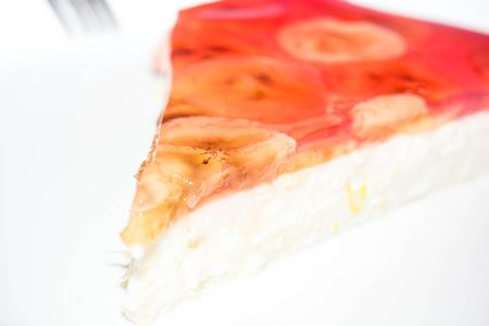 Cottage cheese cake with banana slices and gelatin on isolated background