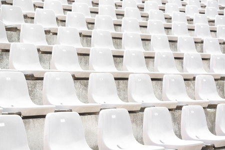 Empty white stadium stand rows with sunlight