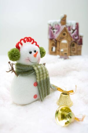 Snowman with bells standing in front of the house. Stock Photo