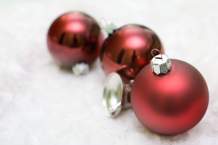 Red christmas balls in a row with a silver bell. Stock Photo