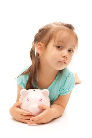 Young little girl holding a piggy bank on isolated white background. Stock Photo